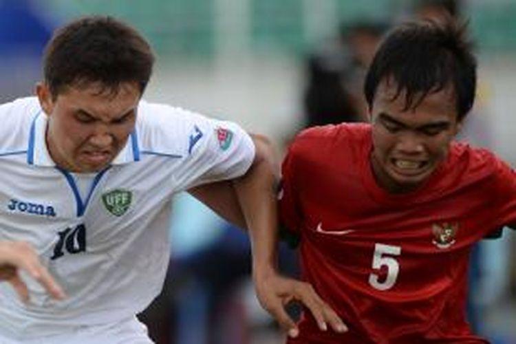 Pemain Indonesia, Muhammad Fatchu Rochman (kanan) saat berebut bola dengan pemain Uzbekistan, Shukurov Otabek pada turnamen sepak bola Piala AFC U-19 di Stadion Thuwunna, Yangon, Myanmar, Jumat (10/10/2014). Indonesia menyerah 1-3.