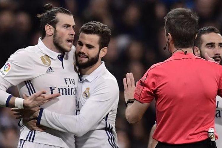 Bintang Real Madrid, Gareth Bale (kiri), berusaha diredam rekan setimnya Nacho Fernandez (dua dari kiri) saat berdebat dengan wasit dalam pertandingan melawan Las Palmas di Santiago Bernabeu pada 1 Maret 2017.
