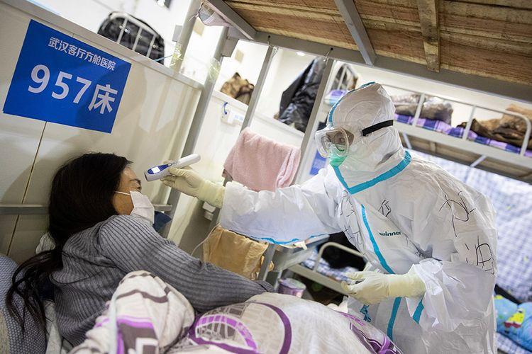 Pasien dengan gejala ringan virus corona COVID-19 diperiksa suhu tubuhnya oleh petugas medis saat menjalani perawatan di sebuah pusat pameran yang diubah menjadi rumah sakit darurat di Wuhan, Hubei, China (17/2/2020). Data hingga Rabu (19/2/2020) ini, korban meninggal akibat virus corona di China sudah mencapai 2.000 orang setelah dilaporkan 132 kasus kematian baru.