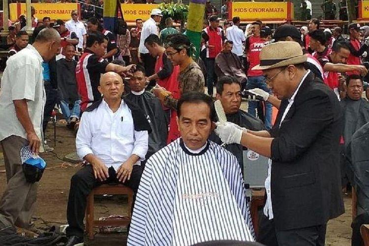 Presiden Joko Widodo dipangkas rambutnya oleh Herman, tukang cukur langganannya di acara cukur massal yang diadakan di Situ Bagendit, Kecamatan Banyuresmi, Kabupaten Garut, Jawa Barat, Sabtu (19/1/2019).