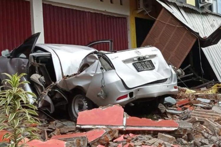 Sebuah mobil dan bangunan rusak akibat gempa bumi, di Mamuju, Sulawesi Barat, Jumat (15/1/2021).