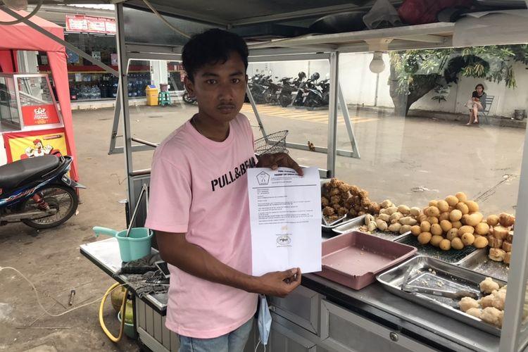 Acep (20), pedagang gorengan di Jalan Taman Margasatwa Ragunan menunjukkan surat pemberitahuan pabrik tahu dan tempe yang mogok produksi di tempatnya berjualan pada Minggu (3/1/2021) siang.