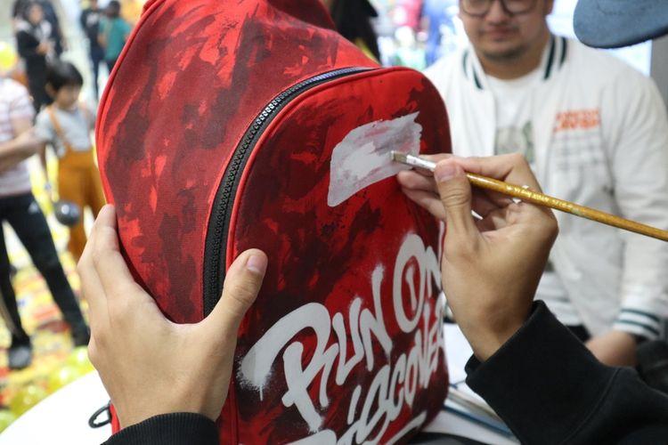 NeverTooLavish melakukan live painting di 1 tas Wilio yang nantinya tas tersebut akan dilelang dan hasilnya akan disumbangkan untuk organisasi anak yang membutuhkan.