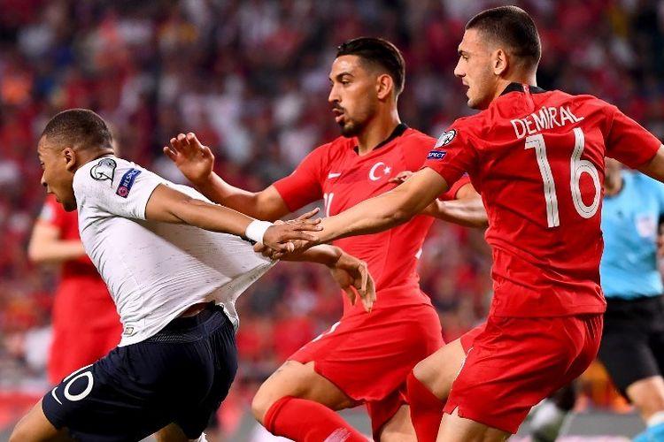 Merih Demiral (kanan) dan Irfan Kahveci mencoba menahan laju Kylian Mbappe pada pertandingan Turki vs Perancis dalam kualifikasi Euro 2020 di Stadion Buyuksehir Belediyesi, 8 Juni 2019.