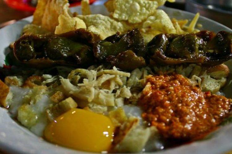 Bubur ayam spesial dengan tambahan kuning telur, emping, dan sate ampela.