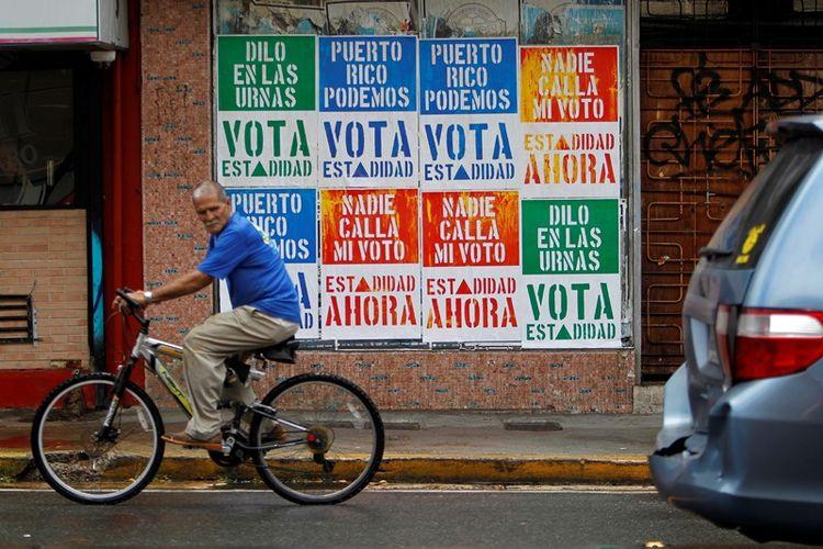 Seorang pria bersepeda melintasi poster yang mengajak rakyat Puerto Rico mendukung upaya menjadikan negeri itu negara bagian ke-51 Amerika Serikat.