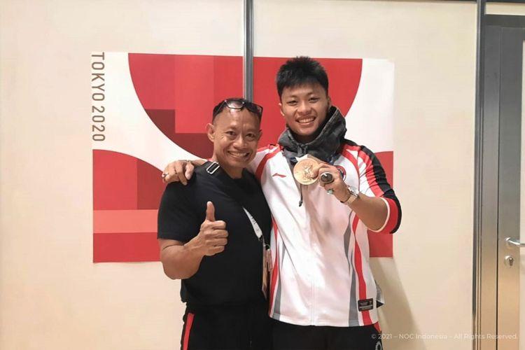 Erwin Abdullah (kiri) bersama anaknya, Rahmat Erwin Abdullah (kanan), yang berhasil meraih medali perunggu angkat besi kelas 73 kg putra di Olimpiade Tokyo 2020.