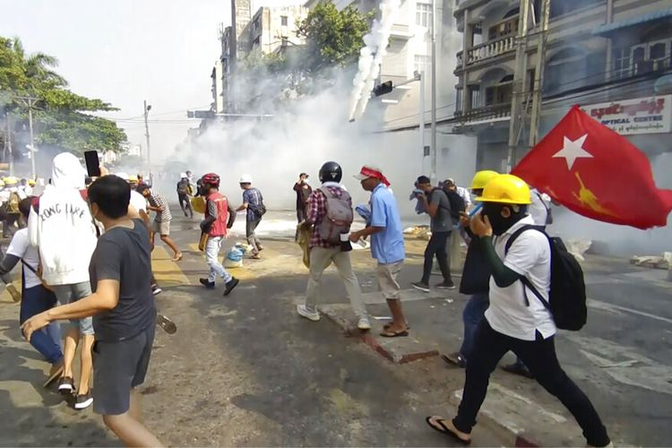 Dalam gambar dari sebuah video ini, pengunjuk rasa anti-kudeta bereaksi ketika asap dari gas air mata naik di Yangon, Myanmar Minggu (28/2/2021).