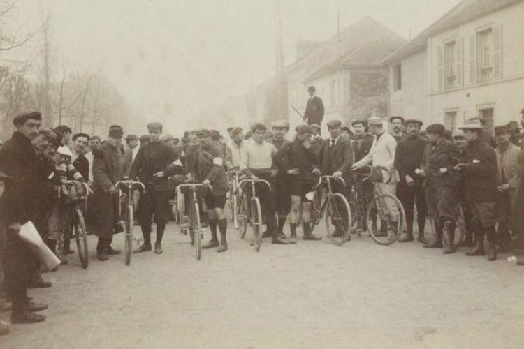 Suasana garis start balapan sepeda Paris Roubaix tahun 1899, di mana pesepeda masih memakai flat cap