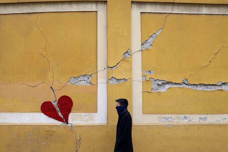 Seorang pria berjalan di samping bentuk hati yang rusak terbuat dari wol yang dibuat oleh perancang Kroasia Ivona, yang diletakkan di sebuah bangunan di pusat kota Zagreb, Kroasia, Rabu (25/3/2020), saat negeri tersebut melawan penyebaran penyakit virus corona (COVID-19) dan pasca-bencana gempa bumi yang terjadi di Kroasia pada 22 Maret lalu.