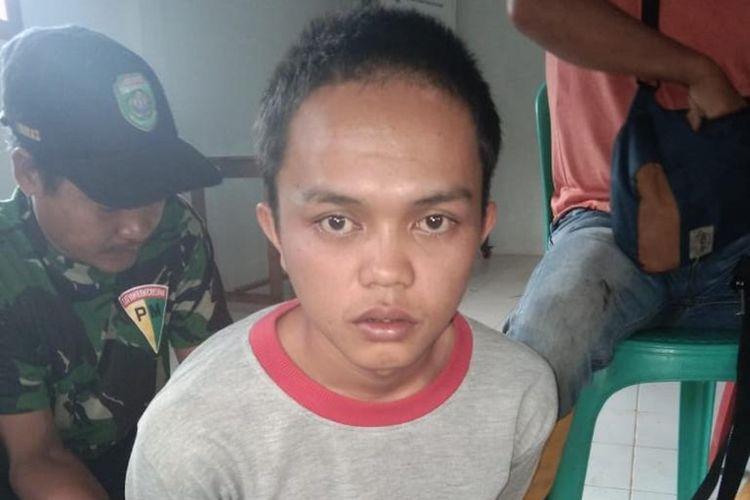 Edian Saputra (23) yang merupakan pelaku pembunuhan ibu kandungnya sendiri, ketika berada di Polsek Pulau Beringin, Kabupaten OKU Selatan, Sumatera Selatan.
