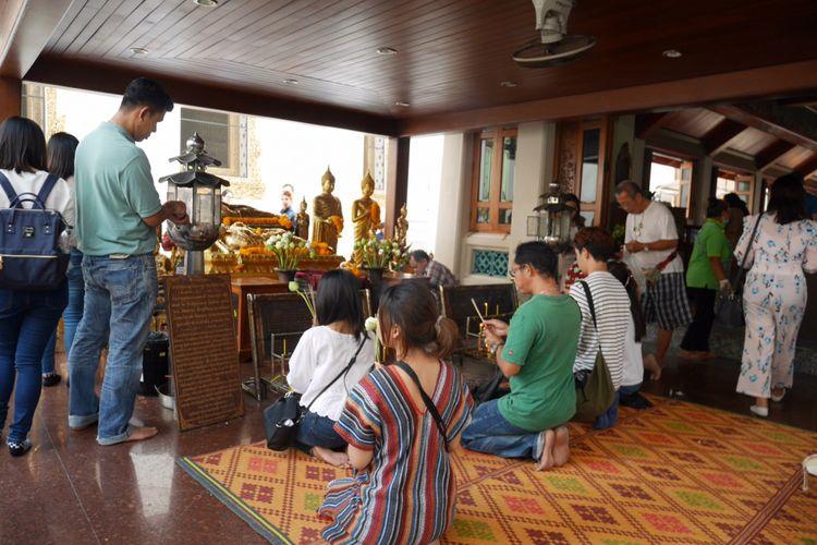 Berdoa di Wat Pho salah satu kuil ikonik di Bangkok, Thailand, Mingu (4/2/2018).