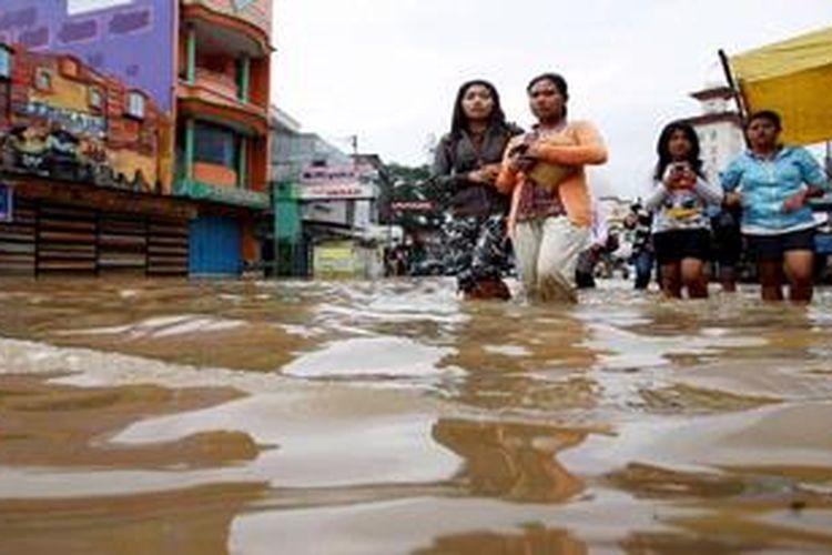 Sejumlah warga melintasi Jalan Raya Dayeuhkolot, Kabupaten Bandung, Jawa Barat, yang terendam banjir, Jumat (19/4/2013). Ribuan pemukiman warga, bahkan kawasan pertokoan dan pasar, di wilayah Dayeuhkolot serta pemukiman warga di Baleendah sudah tiga pekan terendam banjir luapan Sungai Citarum. Jalur lalulintas yang terputus memaksa warga, termasuk para buruh pabrik di kawasan tersebut, harus melintasi genangan air untuk menuju pemberhentian kendaraan dengan jarak berjalan kaki sekitar 2 kilometer.