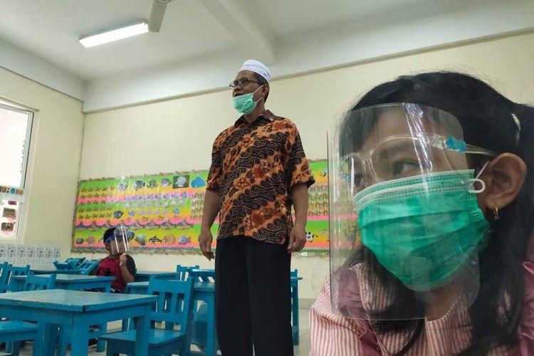 Para murid Sekolah Dasar (SD) Yayasan IBA Palembang menggunakan sistem drive thru dalam Masa Pengenalan Lingkungan Sekolah (MPLS), Senin (13/7/2020).