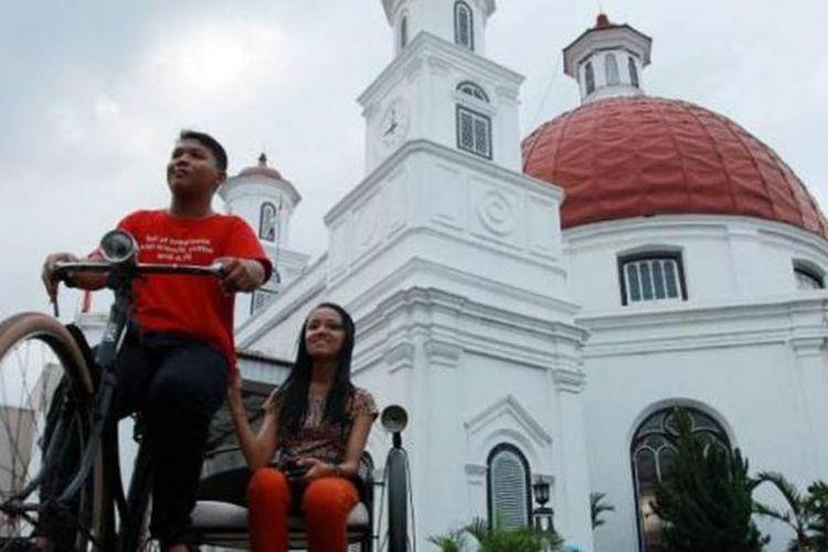 Dua remaja menaiki sepeda kebo tandem di kawasan Kota Lama, Semarang, Jateng, Rabu, (18/9/2013). Dua sepeda karya Komunitas Oase tersebut akan disewakan pada acara Symfoni Kota Lama Sabtu (21/9/2013).