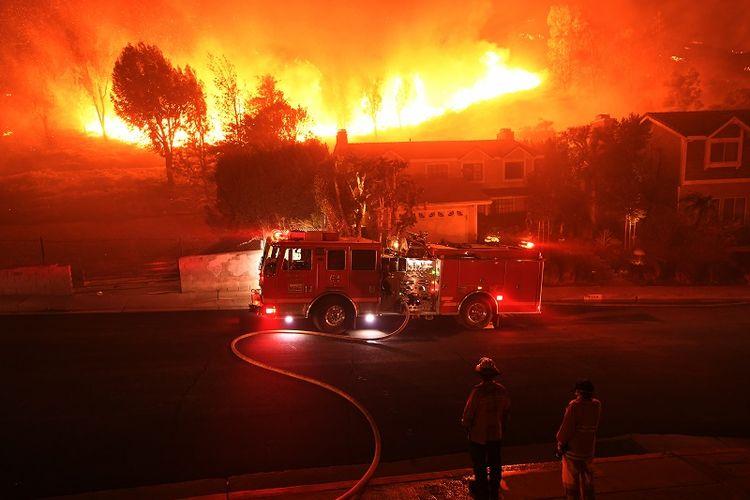 Pasukan pemadam kebakaran California mencoba mengendalikan api yang muncul di belakang sebuah rumah di kawasan West Hills, Jumat (9/11/2018).