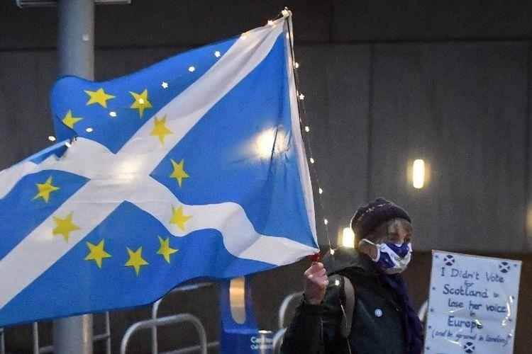Seorang aktivis kemerdekaan anti-Brexit pro-Skotlandia memegang bendera yang mencampurkan bendera UE dan Saltire Skotlandia saat dia berkumpul untuk protes kecil terhadap keluarnya Inggris dari Uni Eropa di luar Parlemen Skotlandia di Edinburgh  (31/12/2020).