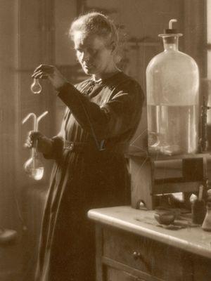 Marie Curie bekerja di laboratoriumnya di Universitas Paris pada 1925. (Historia/REX/Shutterstock.com via Britannica)