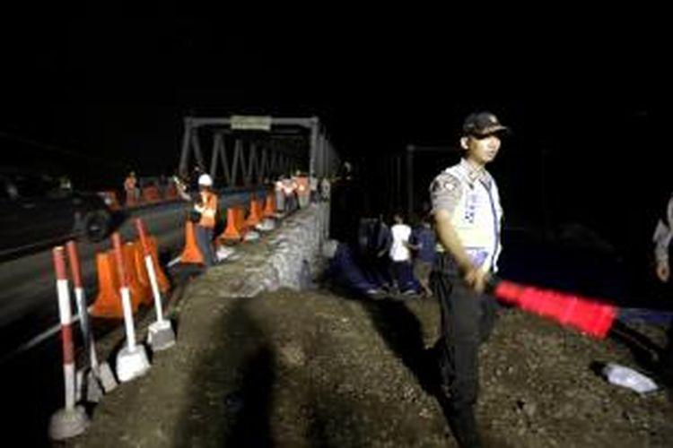 Polisi menjaga proses dibukanya kembali Jembatan Comal Pantura, Pemalang, Jawa Tengah, untuk kendaraan pribadi dan sepeda motor di jalur Jakarta ke Surabaya, Kamis (24/7/2014) pukul 02.30. Lalu lintas untuk jalur Surabaya - Jakarta masih diarahkan ke jalan alternatif. KOMPAS.COM/FIKRIA HIDAYAT