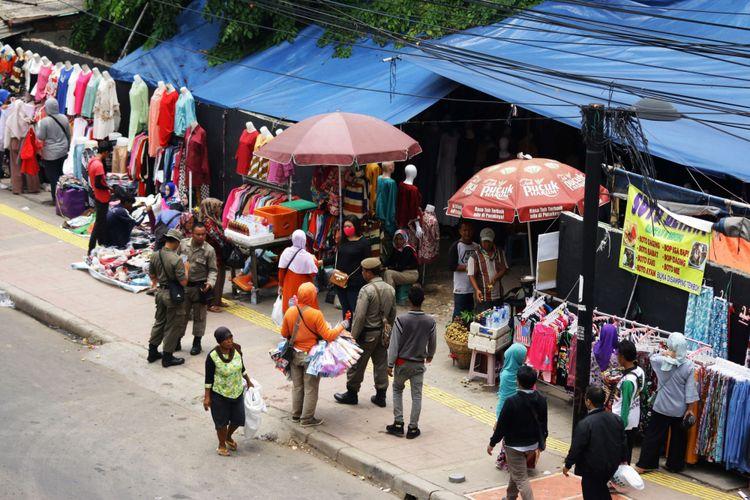 Sejumlah petugas Satpol PP berjaga di atas trotoar yang dipenuhi Pedagang Kaki Lima (PKL) di Tanah Abang, Jakarta, Rabu (18/10/2017). Meskipun sudah ditertibkan, para PKL tersebut masih saja berjualan di atas trotoar dengan alasan harga sewa toko yang sangat mahal.