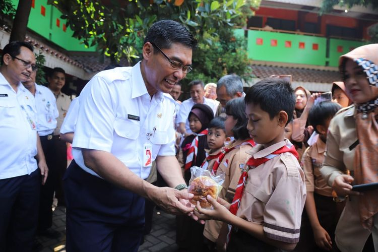 Kepala Dinas Pendidikan DKI Jakarta Ratiyono memberikan makanan kepada murid SD 03 dan 04 Penjaringan dalam rangka launching program Pemberian Penyediaaan Makanan Tambahan Anak Sekolah (PMTAS), Rabu (27/3/2019).