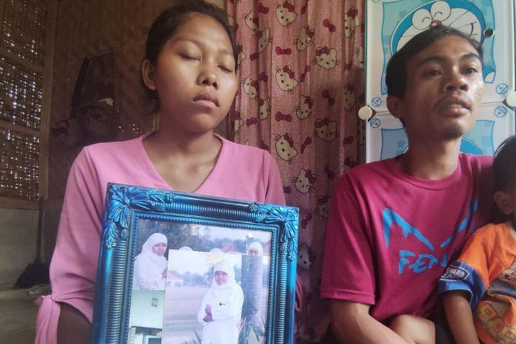 Repi bersama suaminya memegang poto Yeti, ibu kandungnya yang jadi pekerja migran asal Cianjur, Jawa Barat. Yeti yang hilang kontak selama 17 tahun, akhirnya ditemukan.