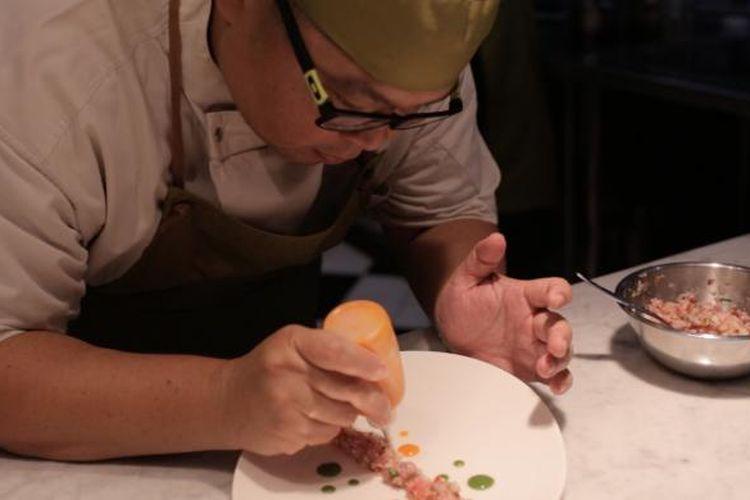 Chef Ragil sedang menghias makanan di piring saji.