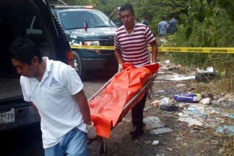 Dua petugas polisi Veracruz mengangkat jenazah tanpa kepala yang menjadi korban pembunuhan kartel narkoba di sana.