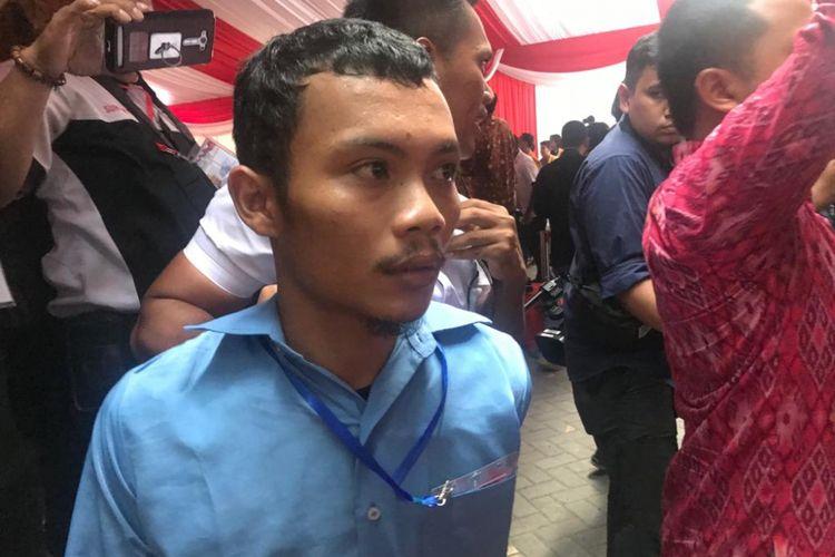 Salah satu pengunjuk rasa yang berteriak-teriak dan membentangkan karton bertuliskan tuntutan saat acara Presiden Joko Widodo di Muktamar Pelajar Muhammadiyah, Sidoarjo, Jawa Timur, Senin (19/11/2018).