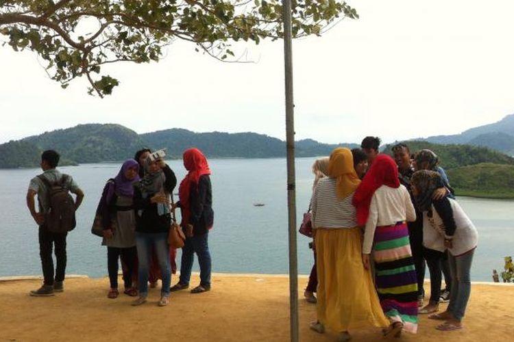 Para wisatawan sedang berfoto di Puncak Mandeh, Kecamatan Tarusan, Kabupaten Pesisir Selatan, Sumatera Barat, Kamis (14/5/2015).