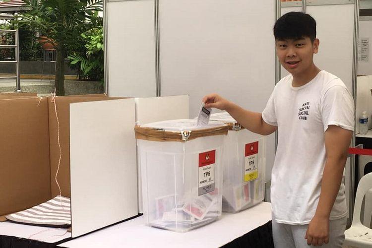 Seorang pemilih milenial memasukan surat suaranya ke kotak suara PPLN Singapura yang terbuat dari plastik transparan sehingga pemilih dapat melihat isi kotak dari luar. (KOMPAS.com/ERICSSEN)