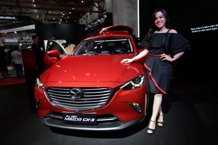 Sales promotion girl berpose di samping Mazda CX-3 generasi terbaru saat ajang Indonesia International Motor Show (IIMS) 2017 di JI Expo, Kemayoran, Jakarta, Jumat (28/4/2017).