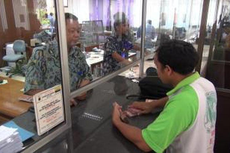 Seorang warga dilayani petugas saat akan menukarkan uang pecahan Rp 10 ribu di Bank Indonesia Pewakilan Tegal. Menjelang Pileg, kenaikan penukaran uang di Kantor BI Perwakilan Tegal, naik hingga tiga kali lipat.