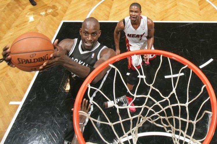 Pebasket Brooklyn Nets, Kevin Garnett (kiri) melakukan lay up di depan pemain Miami Heat, Chrish Bosh, saat kedua tim bertemu di Barclays Center pada lanjutan kompetisi NBA, Jumat (1/11/2013).