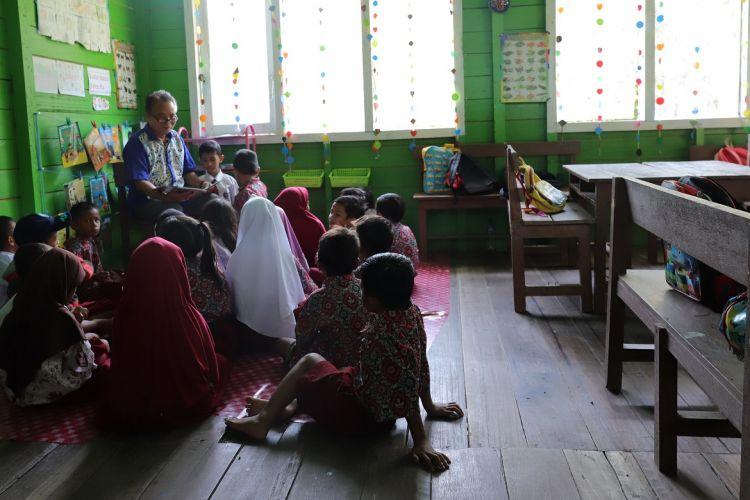Kuleh Lenjau guru kelas 1 SDN 008 Baratan, Bulungan membacakan cerita kepada anak sebelum pembelajaran dimulai. Melalui KKG, sekolah-sekolah di Bulungan didorong untuk mengembangkan program budaya sekolah.