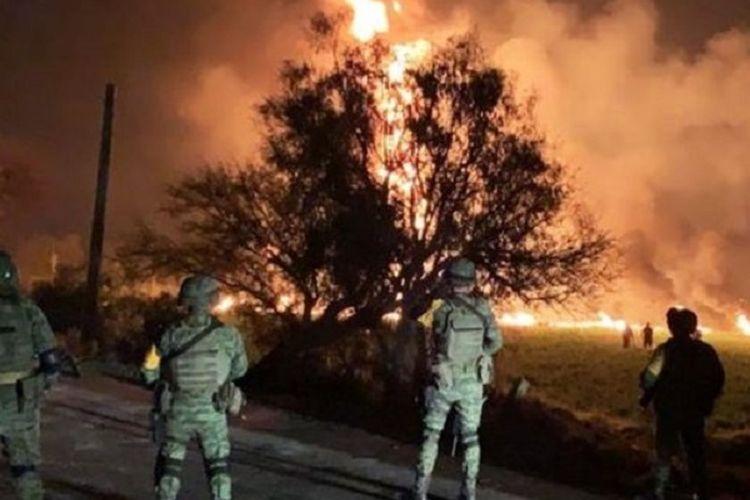 Tentara melihat kobaran api dari pipa minyak ilegal yang meledak di Tlahuelilpan, Meksiko, pada Jumat (18/1/2019).