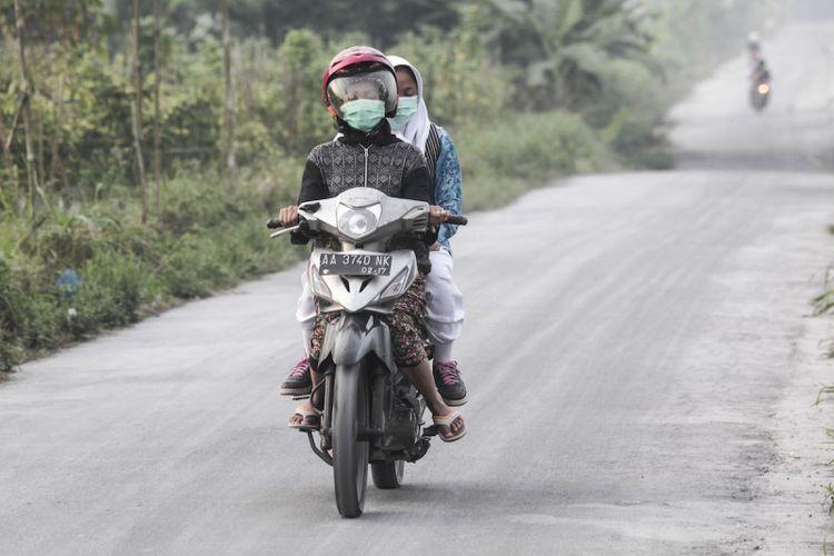Warga melintasi jalan yang diselimuti abu vulkanik letusan Gunung Merapi di Muntilan, Jawa Tengah, Kamis (24/5). Sejumlah daerah di kawasan Magelang, Jawa Tengah terkena hujan abu vulkanik akibat letusan Gunung Merapi yang terjadi pada Kamis (24/5) pukul 02.56 WIB dengan durasi 4 menit dan tinggi kolom (asap letusan) 6.000 meter. ANTARA FOTO/Andreas Fitri Atmoko/foc/18.