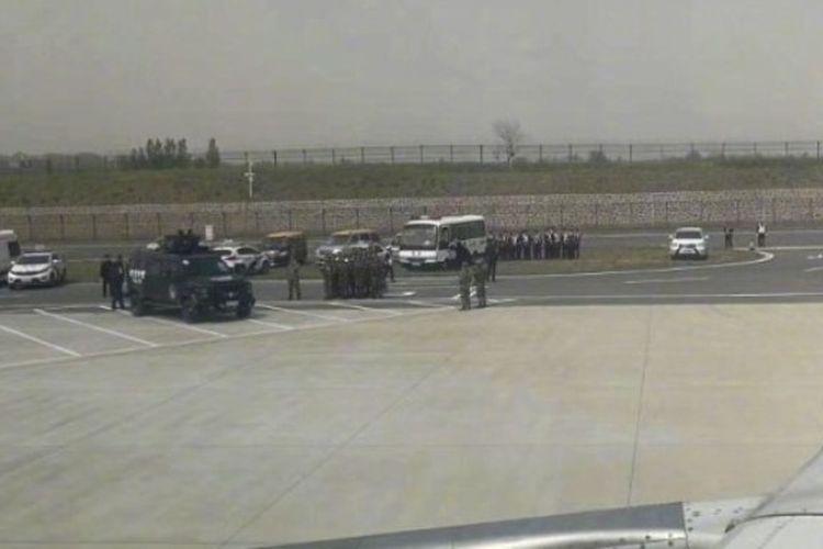 Personil darurat bersiap di landasan di Bandara Internasional Zhengzhou Xinzheng di Provinsi Henan, setelah sebuah pesawat mendarat darurat karena kasus penyanderaan, Minggu (15/4/2018).