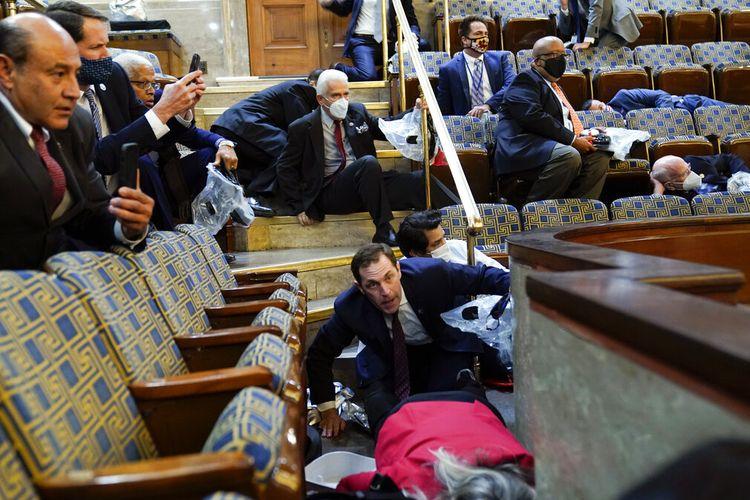 Anggota Parlemen AS berlindung di serambi ruang parlemen ketika pengunjuk rasa mencoba masuk ke House Chamber di Gedung Capitol pada Rabu (6/1/2021).