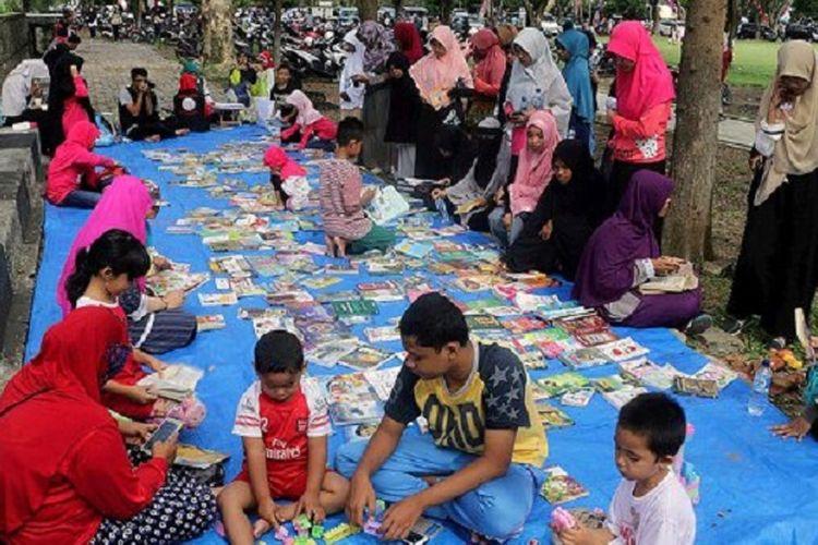 Warga membaca buku di arena pustaka di lapangan terbuka Blang Padang, Banda Aceh, Aceh, Minggu (5/3). Komunitas Rumah Baca Aneuk Nanggroe membuka pustaka di ruang publik setiap hari Minggu untuk mendekatkan buku dengan warga sehingga menumbuhkan minat baca.