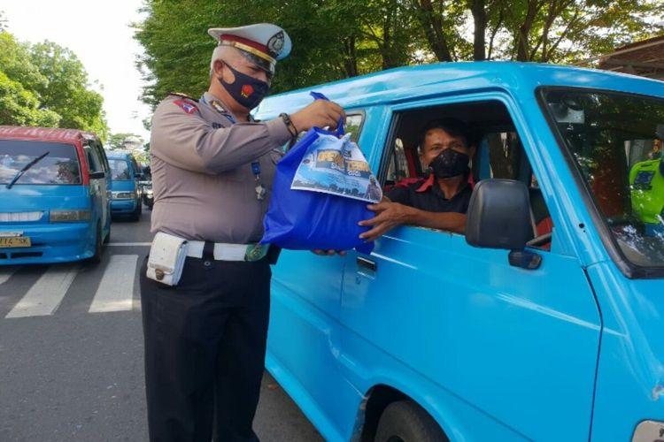 Personel Satlantas Polresta Manado membagikan masker dan paket sembako gratis kepada masyarakat pengguna jalan dalam pelaksanaan Operasi Zebra Samrat hari ke-8, Senin (2/11/2020).