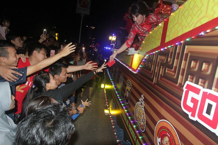 Wali Kota Singkawang, Tjhai Chui Mie saat membagikan angpau kepada masyarakat yang menyaksikan pawai lampion dalam perayaan Imlek dan Cap Go Meh di Singkawang, Kalimantan Barat (28/2/2018).
