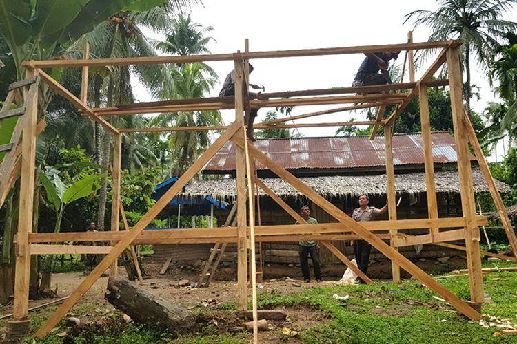 Bripka Deni Saputra, Kanit Binmas Polsek Makmur, Polres Bireuen sedang membangun rumah untuk Usman (65) warga miskin di Desa Pulo Teungoh, Kecamatan Makmur, Bireuen, Jumat (27/10/17).
