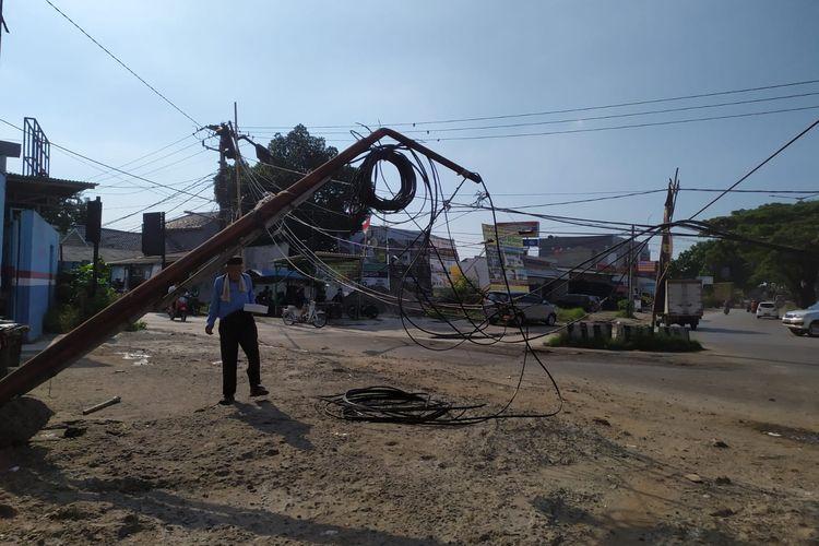 Seorang warga melintas di bawah tiang kabel telepon yang nyaris tumbang lantaran terseret kontainer di Jalan Ciater, Tangerang Selatan, Kamis (16/9/2021).