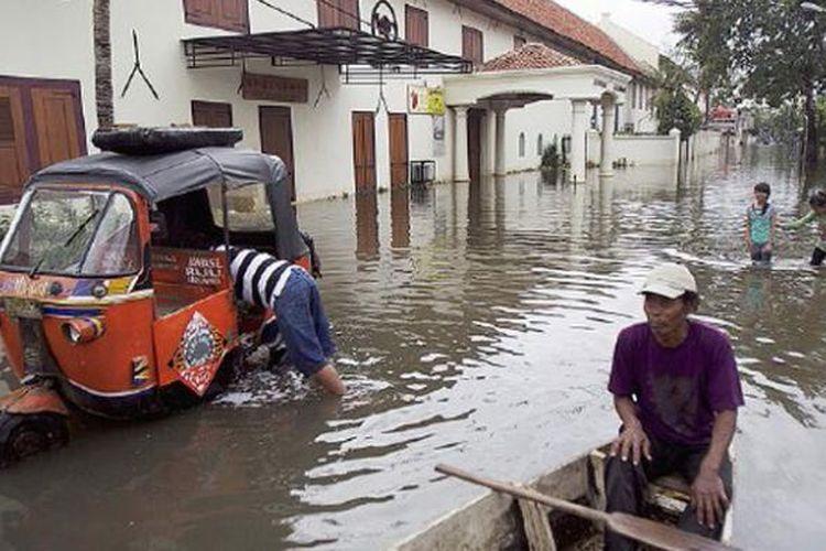 Tukang perahu menunggu warga yang menyeberang di Jalan Kakap, Jakarta Utara, Senin (21/1/2015). Banjir sudah lima hari menggenangi kawasan ini.