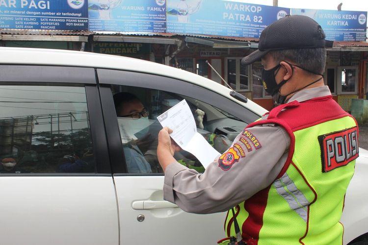 Seorang anggota polisi memeriksa surat keterangan hasil antigen seorang pengendara dalam giat penyekatan di check point Seger Alam, Ciloto Puncak, Kabupaten Cianjur, Jawa Barat, Kamis (29/4/2021)