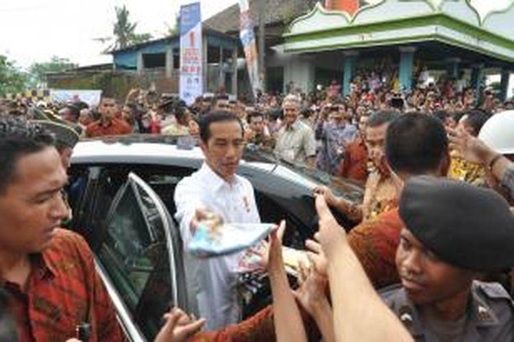 Presiden Jokowi membagikan kaos dan buku usai keluar dari lokasi groundbreaking Rusunawa, Kelurahan Gedanganak, Ungaran Barat, Kabupaten Semarang, Rabu (29/4/2015) siang.