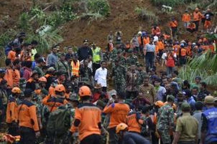 Presiden Joko Widodo (kemeja putih) mendatangi lokasi tanah longsor di Desa Sampang, Kecamatan Karangkobar, Banjarnegara, Minggu (14/12). Jokowi meminta kepada petugas dan relawan untuk mengutamakan pencarian korban yang diduga masih tertimbun longsor.