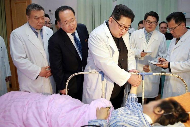 Pemimpin Korea Utara Kim Jong-Un mengunjungi seorang korban kecelakaan bus di sebuah rumah sakit, Senin (23/4/2018). (KCNA via KNS/AFP)