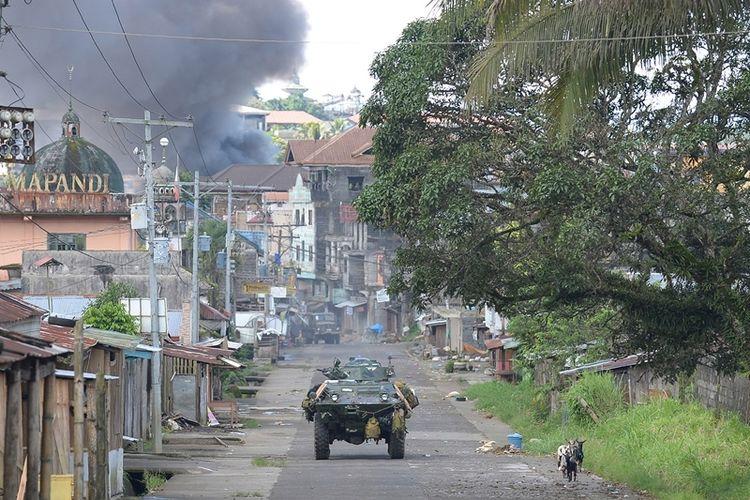 Sebuah kendaraan tempur milik marinir Filipina bergerak di jalanan kota Marawi yang lengang, sementara di belakangnya asap hitam mengepul dari sebuah bangunan yang mungkin terkena tembakan roket.